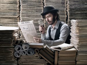 Young man in old fashioned costume doing research among newspapers